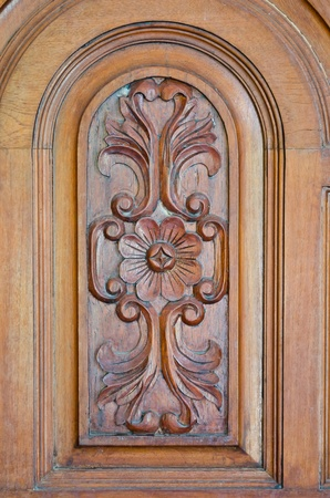 A part of a classic door carved as a flower and some leaves photo