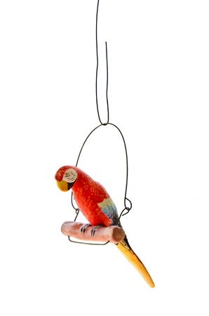 An isolated red parrot model on a perch
