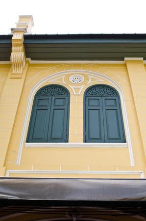 Green classic windows with yellow wall taken from an old house row in Ratanakosin Island, Bangkok Stock Photo - 13492778