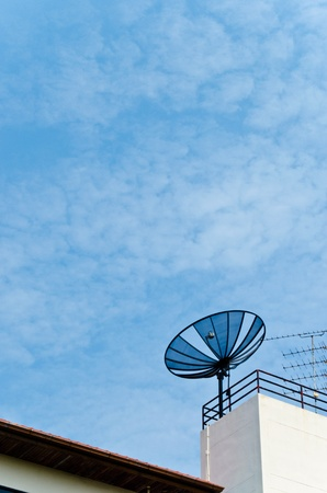 A black antenna on a rooftop with the blue sky photo