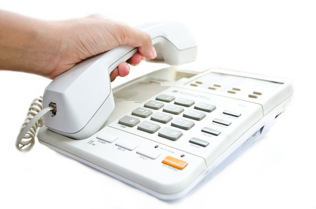 A hand holding a white telephone Stock Photo