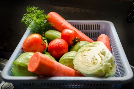 Carrots, tomatoes, cucumbers, cabbage, and guava in a basket Stock Photo