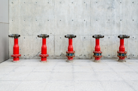 five red fire hydrants on the gray background