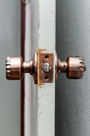 bronze round door knob on a gray door