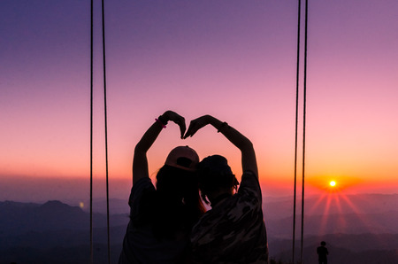 silhoutte of two people making a heart shape with twilight