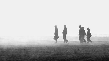 group of five people walking in a land with dust