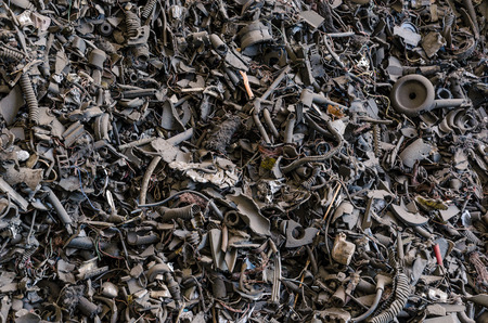 metal waste in different formed arranged in piles in dark tone