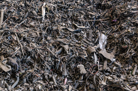 metal waste in different formed arranged in piles in a dark tone