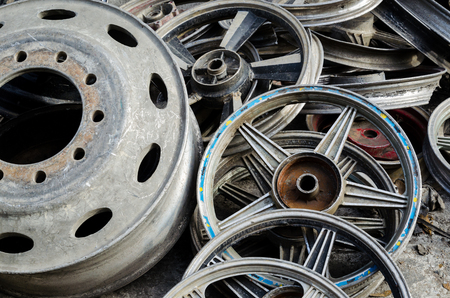 pile of used aluminium wheels of different sizes and designs
