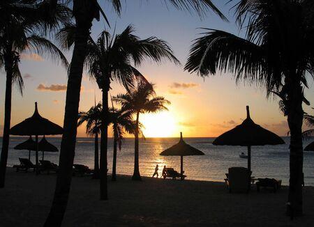 Un tramonto sul mare, con palme da cocco e capanne sagome