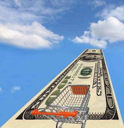 Shopping cart on a $100 dollar bill over sky with clouds. Stock Photo