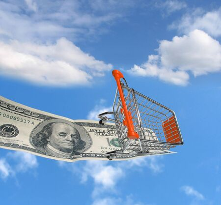 pitfall: Shopping cart on a $100 dollar bill over sky with clouds. Stock Photo