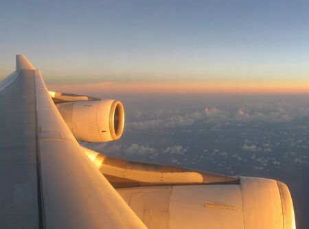 Airplane wing at sunset above clouds Stock Photo