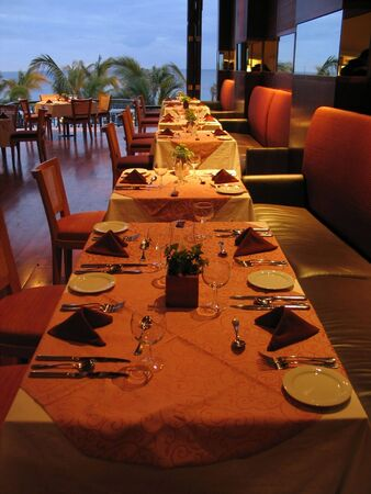 Prepared table in a restaurant under artificial light Stock Photo