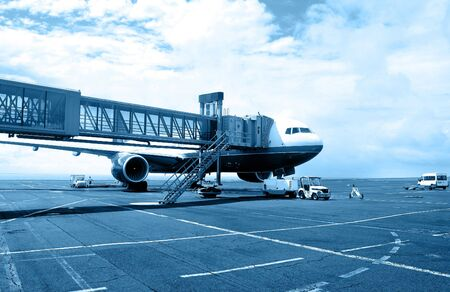 Wide angle view of airplane on tarmac being serviced. Monochrome blue version Stock Photo