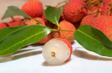 Lychees in my garden. Focus on peeled one. Stock Photo