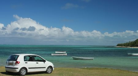 White small car on green grass by the beach photo