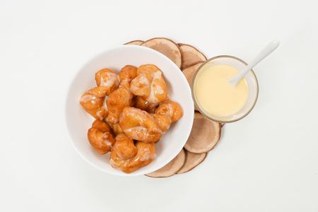 Bread (deep fried stick) and Sweetened condensed milk on white background