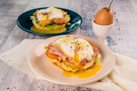 Healthy breakfast with poached egg with green salad on a wooden table closeup