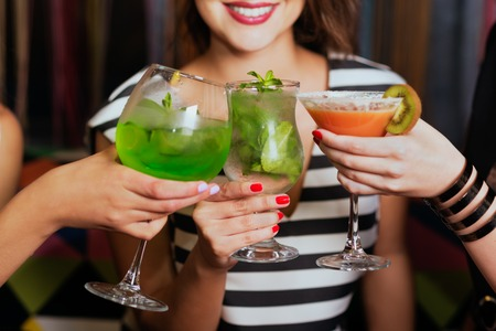 Girls with cocktails toasting against flying colours shot closeup