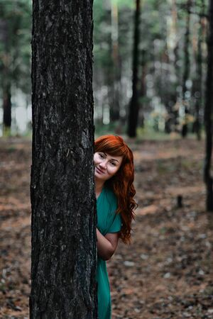 Red-haired girl in the woods. Fantasy concept
