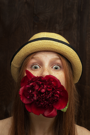 Red-haired girl with red flower photographed in the studio