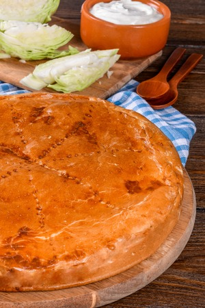 Home pie on a wooden table is shot close-up in the decor