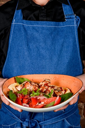 A man in a black shirt and a denim apron keeps the dish shot close-up Stock Photo