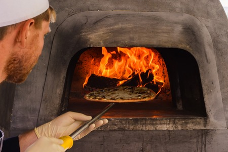 The pizza oven with fire is shot close-up in natural light