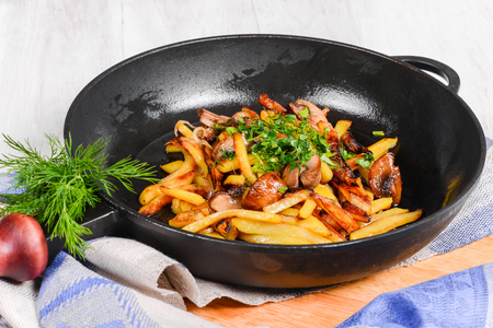 Fried potatoes with mushrooms in a frying pan shot off close-up Imagens