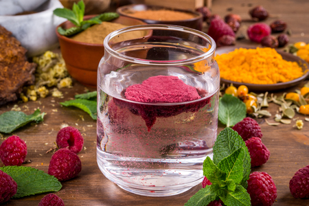 Raspberry extract stir in the water shot close-up
