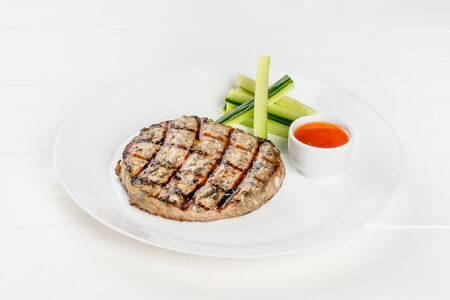 Grilled cutlet on a white plate shot isolated on a white background
