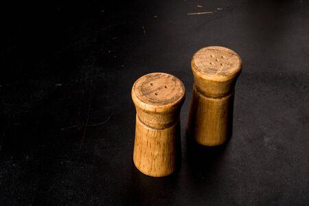 Salt and pepper in wooden salt shakers on a black background. Close-up shot