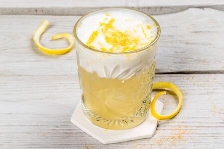 Cocktail with egg and lemon in a glass cup on a wooden white background Banque d'images - 135481559