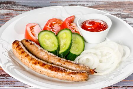 Sausages with vegetables on a white plate on a background shot closeup