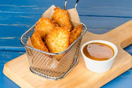 Close-up shot of chicken nuggets with sauce on a wooden board