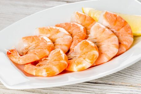 Cooked shrimp on a white plate with lemon. Close-up shot