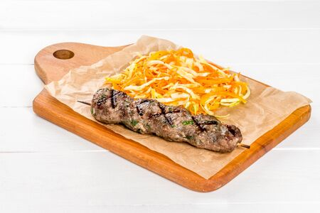 Lulia kebab with vegetables on a wooden board and white background, closeup shot