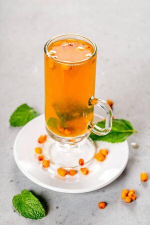 Sea buckthorn tea in a transparent glass cup. Close-up shot
