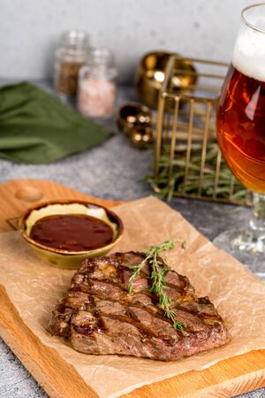 Grilled steak served with beer and sauce shot in decor