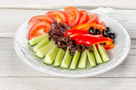 Vegetable white plate with cucumbers, tomatoes, peppers, olives shot on a wooden white background