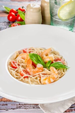 Shrimp pasta in a white plate shot in decor on a wooden background Stock Photo