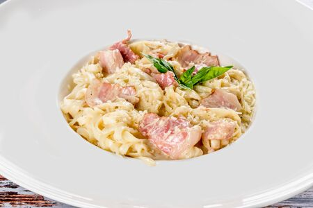 Carbonara pasta with bacon in a white plate shot close-up Stock Photo