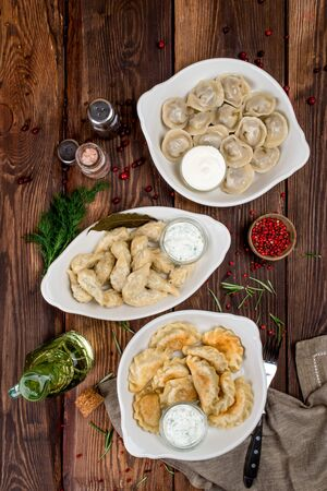 Dumplings and dumplings with sour cream and pepper shot on a wooden background from above