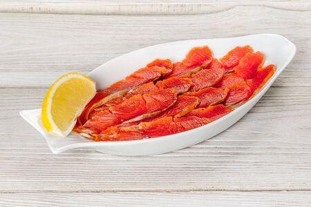 Salmone rosso affettato su un piatto bianco con limone Archivio Fotografico