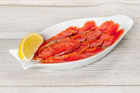 Sliced sockeye salmon on a white plate with lemon