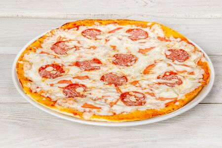 Pepperoni pizza with sausage and cheese on a white plate shot on a wooden background