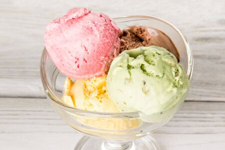 Close-up shot of ice cream in a glass dish on a wooden white background Stock Photo