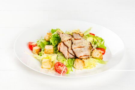 Caesar salad with chicken and fresh herbs in a white plate. Close-up shot