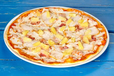 Hawaiian pizza on plates shot on blue wooden background close-up